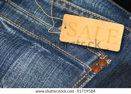 Red Sale Sign With Jeans in Background - stock photo