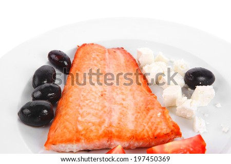 red salmon fish big fillet chunk roast and served on plate with greek white cheese black olives and tomatoes isolated over white background - stock photo