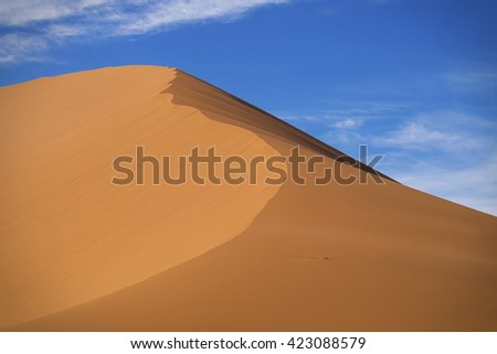 Red sand dune in Namibian desert.  Sunny day, blue sky. (Namibia, South Africa) - stock photo