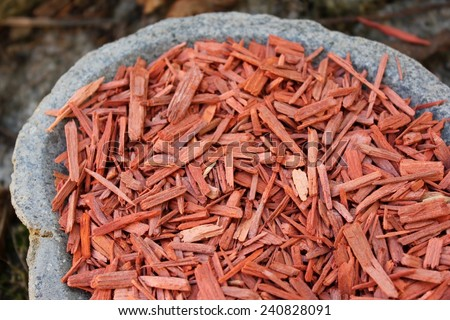 Red Sandalwood incense chips cut (santali rubri from Gabun) in a stone bowl with a forest and stone pathway (bark mulch, leafs) background - stock photo