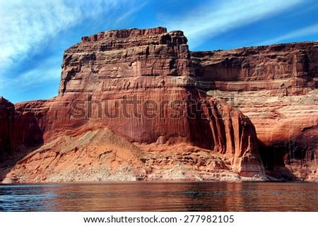 Red sandstone cliff reaches for blue sky along the shores of Lake Powell in Arizona. - stock photo