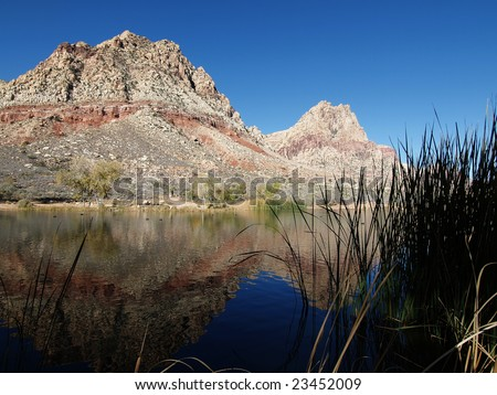 Red sandstone desert peaks reflecting in a spring fed pond. - stock photo