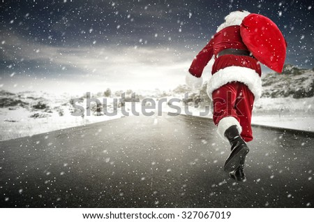 red santa claus and red sack on road of snow  - stock photo