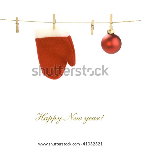Red santa claus glove and Christmas ball on clothes line (with sample text) - stock photo
