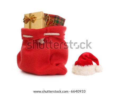 Red Santa Claus hat and bag full of christmas presents over white background - stock photo