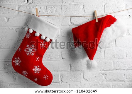 Red Santa Claus hat and sock hanging on white brick wall - stock photo