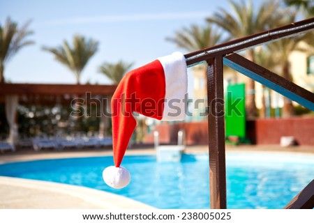 Red Santa Claus hat hanging on a wooden railing next to the pool a summer day - stock photo