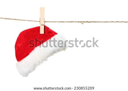 Red Santa Claus hat hanging on the rope isolated on white background - stock photo