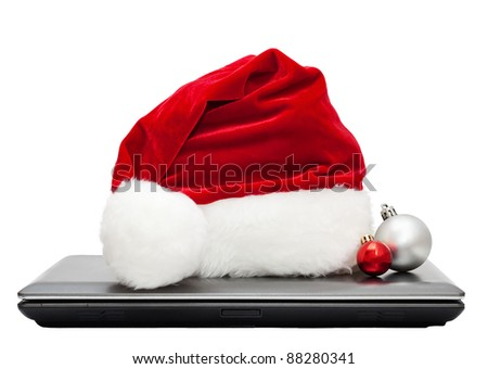 Red Santa hat with two balls on a closed laptop isolated on white background - stock photo