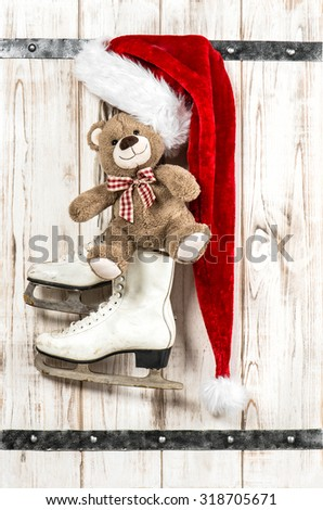 Red Santa's hat, Teddy Bear and white ice skates. Vintage style christmas decorations - stock photo
