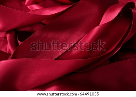 Red satin ribbons in a messy mess texture background - stock photo