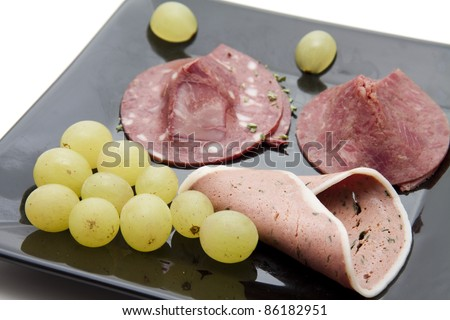Red sausage and liver sausage with grapes - stock photo