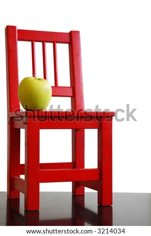 Red school chair and green apple with white background - stock photo