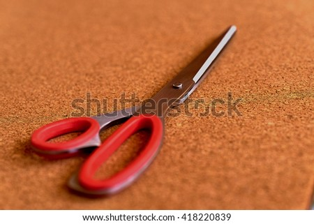 Red scissors on the cork table - stock photo