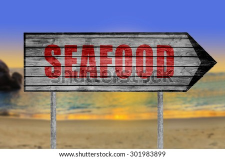 Red Seafood wooden sign with a beach on background