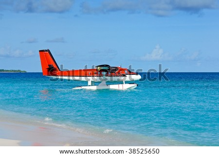 Red seaplane at the beach - stock photo
