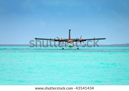 red seaplane in turquoise ocean ready for take off. The water around the turning propellers is a bit disturbed therefore some unsharp areas. - stock photo