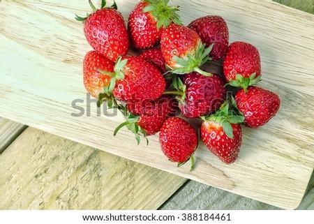 Red seasoning strawberries on wood pad  - stock photo