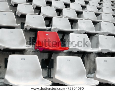 Red seat in White seats on the stadium - stock photo