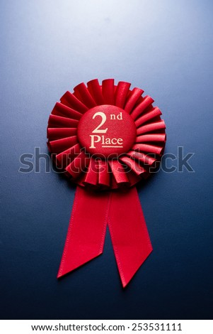 Red second place winner of the socket with a pleated ribbon on a dark background - stock photo