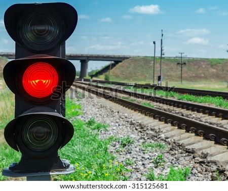 red semaphore near railway. soft focus - stock photo