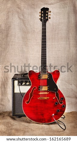 Red Semi Hollow Electric Guitar And Amplifier On Brown Canvas Background