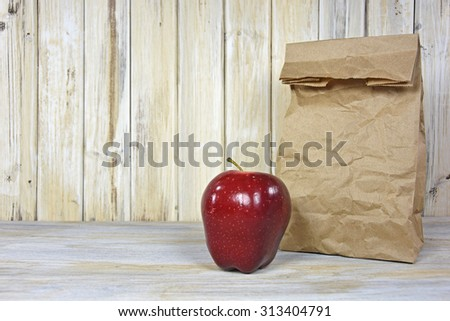red shiny apple and wrinkled brown paper bag on whitewashed wood - stock photo