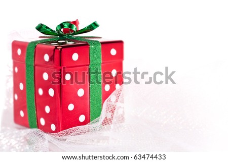 Red shiny polka dot Christmas present on shimmery fabric - stock photo