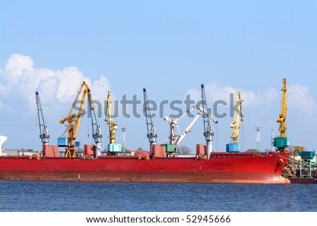 Red ship and port cranes