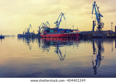 Red ship at the port of loading and unloading of container cranes in the early morning with the reflection in calm water - stock photo