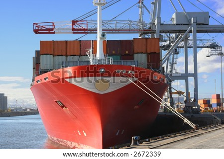 Red ship being unloaded - stock photo