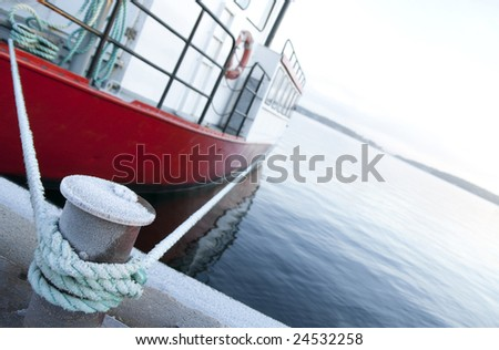 Red ship moored at a quay, focus on bitt and mooring lines. - stock photo