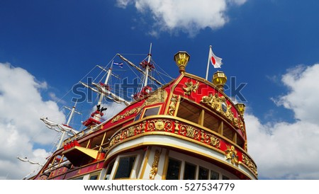 Red ship with Japan flag and blue sky.