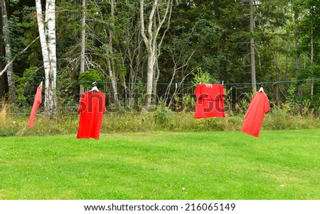 Red shirts on clothesline in sunny day - stock photo
