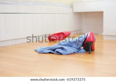 Beautiful Red Shoes And Blue Pants Lay On The Floor Disorder.