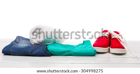 Red shoes and clothes on a white table - stock photo