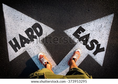Red shoes from above on the white arrows signs for hard and easy way,dilemmas concept - stock photo