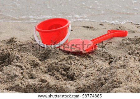Red shovel a shovel with a bucket on a beach