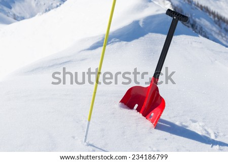 Red shovel and graduated probe for avalanche safety in powder fresh snow. Winter season in the italian Alps. - stock photo