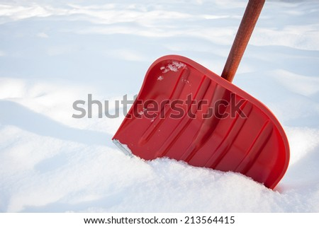 Red shovel for snow removal - stock photo