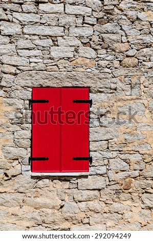 Red Shutters in Stone Wall