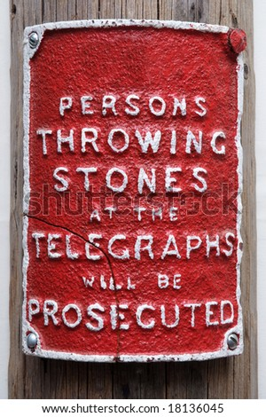 Red sign attached to a telegraph pole warning not to through stones at the pole