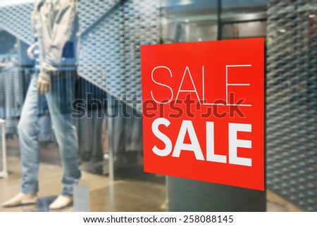 Red sign on a shop window. Sale in a clothing store - stock photo