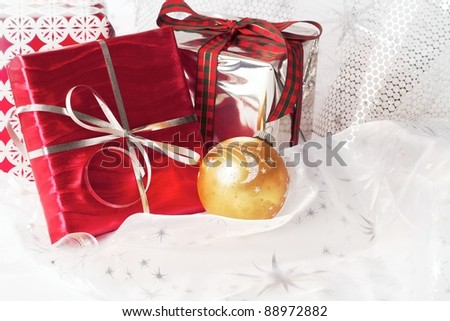 Red, silver, and gold wrapped Christmas gifts with pretty ribbons and ornaments. Silver star translucent fabric backdrop on white. Vertical format with copy space. - stock photo
