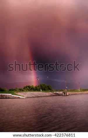 red sky. on the lake. rainbow. red sunset after the rain. Low key, dark background, spot lighting, and rich Old Masters