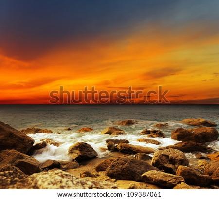 Red sky over a rocky seashore. Sunset landscape. - stock photo
