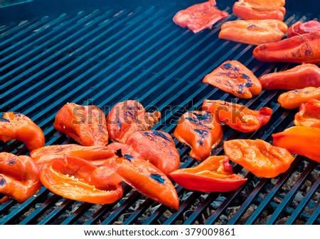 Red sliced of pepper on grill closeup. Fresh paprika baked on an open fire, grill vegetables for garnish. - stock photo