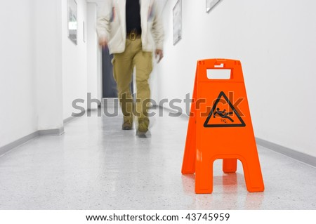 Red Slippery hazard sign in a corridor with legs of a walking person - stock photo