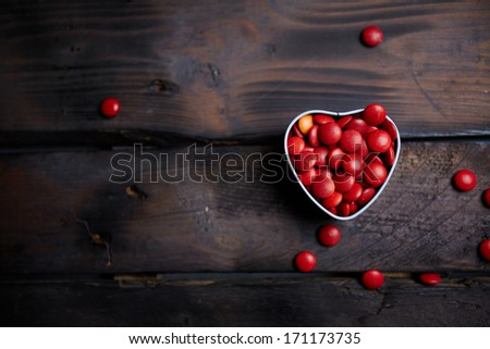 Red small candies in heart shaped box against wooden background - stock photo