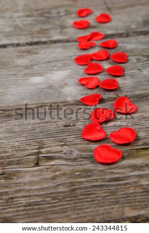Red small hearts on a wooden background. Valentines day background.